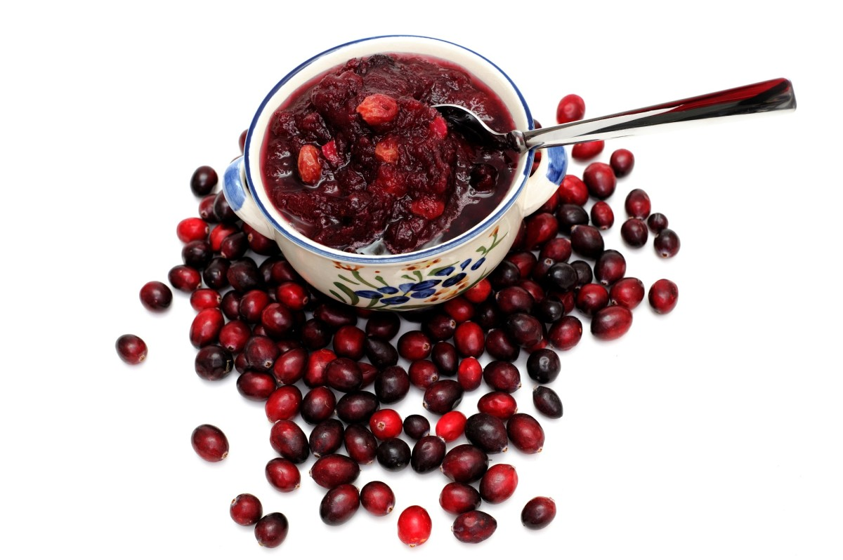 Fresh cranberries on a white background with a bowl of cranberry sauce on top of the berries