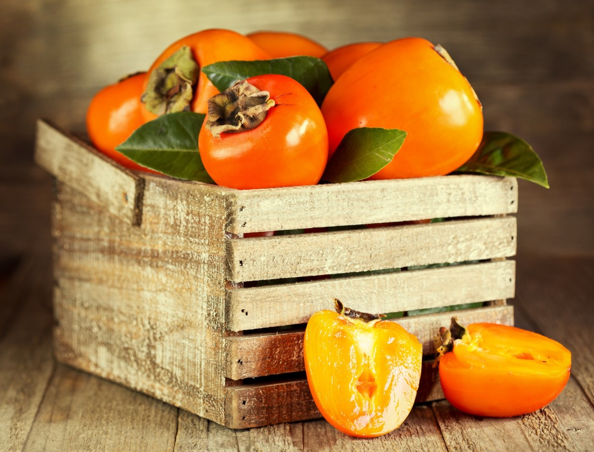 fresh persimmons with leafs in wooden box