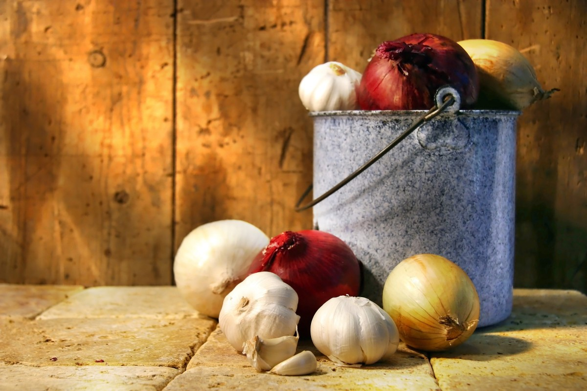 Assortment of different types onions in an old pot